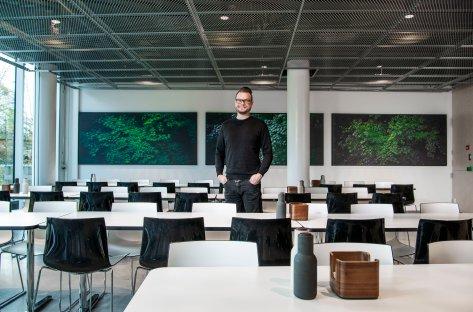 Lyddoktor Halvor Berg står midt i en tom kantine og smiler til kamera.