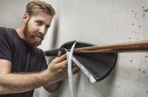 Bilde av en håndverker som isolerer et kobberrør
