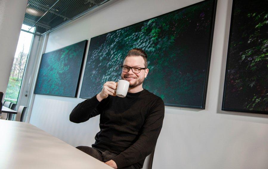 Lyddoktor Halvor Berg sitter i kantina med en kaffekopp i hånd og smiler til kamera.
