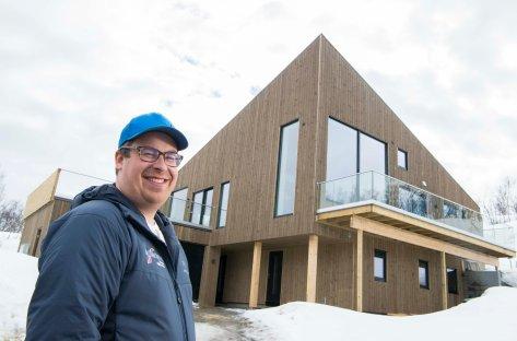 Mann står utendørs foran huset og smiler til kamera