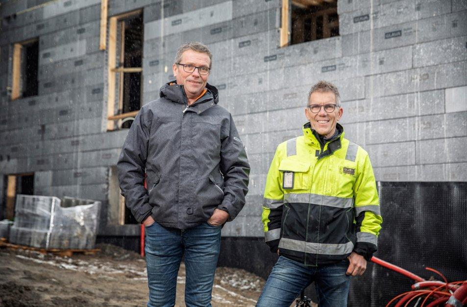 Stein Widar Hagen i S.W. Bygg og Glavas Børre Olsen står foran det aktuelle bygget og smiler til kamera.